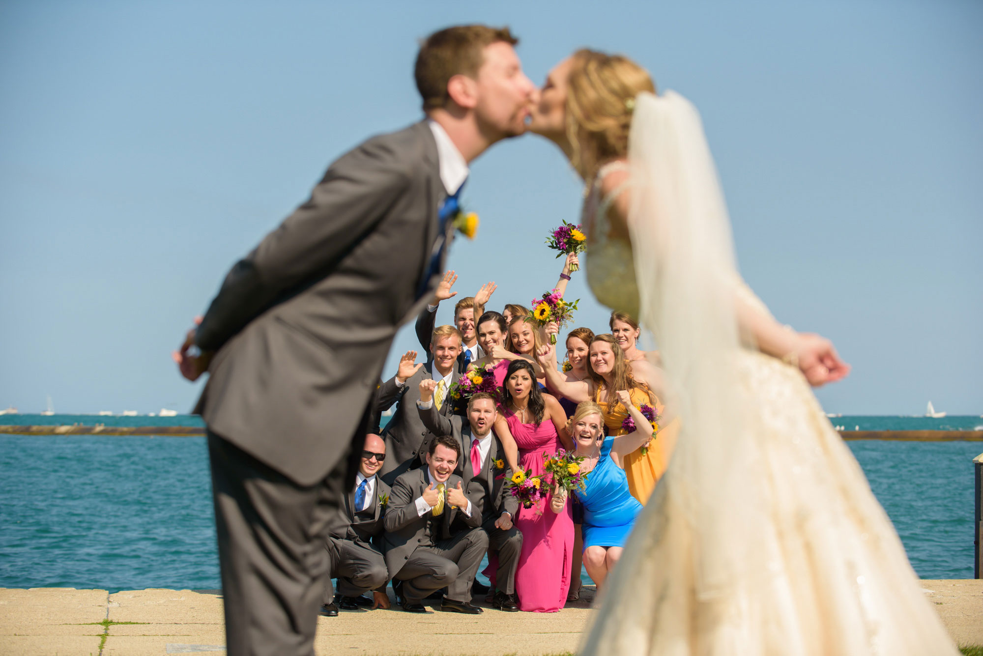 Married couple kiss bridal party cheering